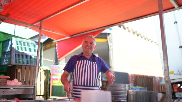 portrait of a senior man in a booth during a street market and cooking pastel - pastel stock videos & royalty-free footage