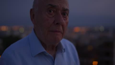 portrait of a senior man looking outside of a window in the dark. - allvarlig bildbanksvideor och videomaterial från bakom kulisserna