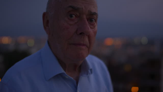 portrait of a senior man looking outside of a window in the dark. - caucasian ethnicity bildbanksvideor och videomaterial från bakom kulisserna
