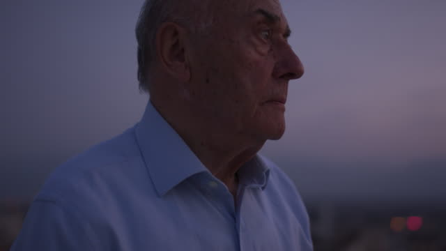 portrait of a senior man looking outside of a window in the dark. - loneliness stock videos & royalty-free footage