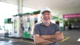 Portrait of a senior man refueling a car at a gas station
