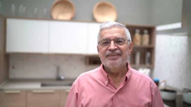 vidéos et rushes de verticale d'un homme aîné restant dans la cuisine - portrait image