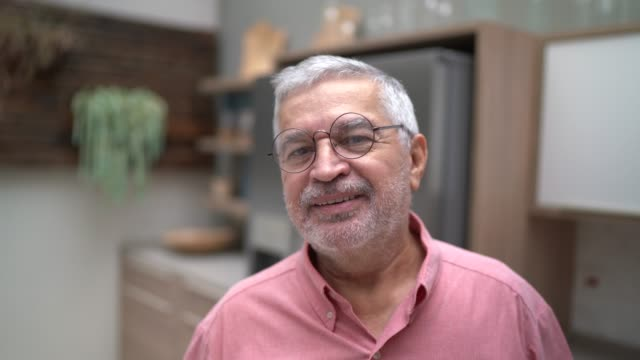 portrait of a senior man standing in the kitchen - one senior man only stock videos & royalty-free footage