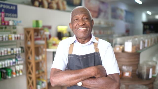 portrait of a senior man standing with arms crossed in a natural product store - responsibility stock videos & royalty-free footage