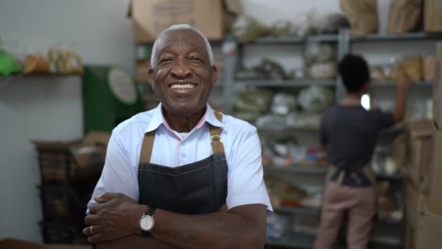 portrait of a senior man standing with arms crossed in the storage room of a natural product store - ethnicity stock videos & royalty-free footage