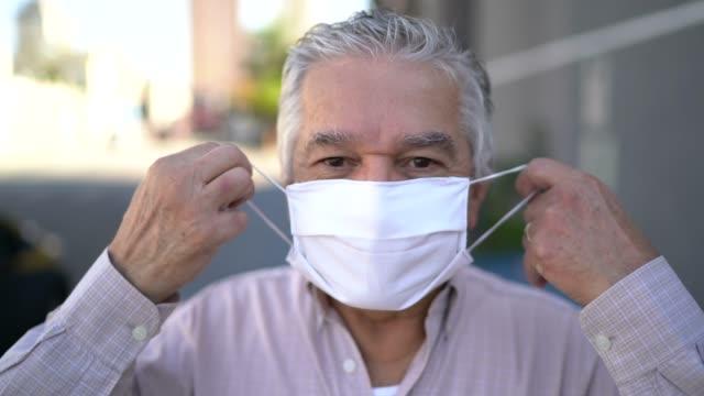 vídeos de stock, filmes e b-roll de retrato de um idoso tirando máscara facial na rua - taking off