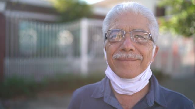 vídeos de stock e filmes b-roll de portrait of a senior man taking face mask off at street - remover