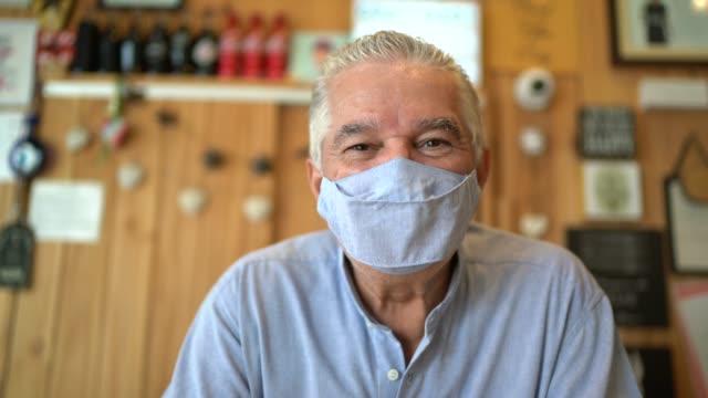 ritratto di un uomo anziano che usa la maschera facciale che lavora in un negozio - mercante video stock e b–roll