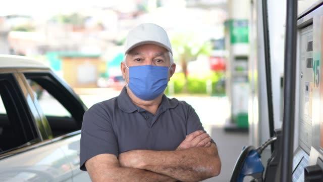 vídeos de stock e filmes b-roll de portrait of a senior man with face mask refueling a car at a gas station - frentista