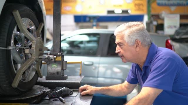 vídeos de stock, filmes e b-roll de retrato de um mecânico sênior em uma auto loja de reparo - pequeno