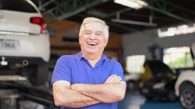 porträt eines leitenden mechanikers in einer autowerkstatt - handwerker stock-videos und b-roll-filmmaterial