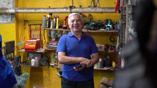 porträt eines leitenden mechanikers, der mit gekreuzten armen in einer autowerkstatt steht - handwerker stock-videos und b-roll-filmmaterial