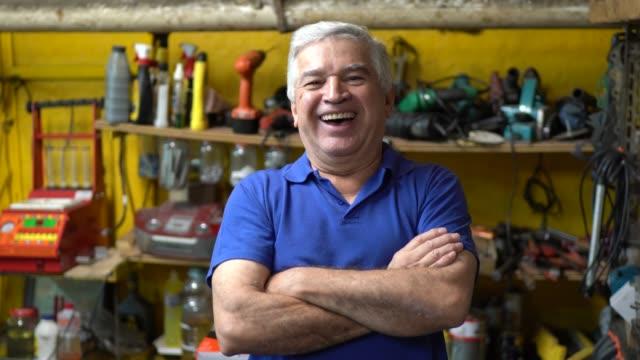 porträt eines leitenden mechanikers, der mit gekreuzten armen in einer autowerkstatt steht - weiser mann stock-videos und b-roll-filmmaterial