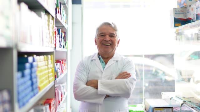 vídeos de stock e filmes b-roll de portrait of a senior pharmacist standing with arms crossed - cultura latino americana