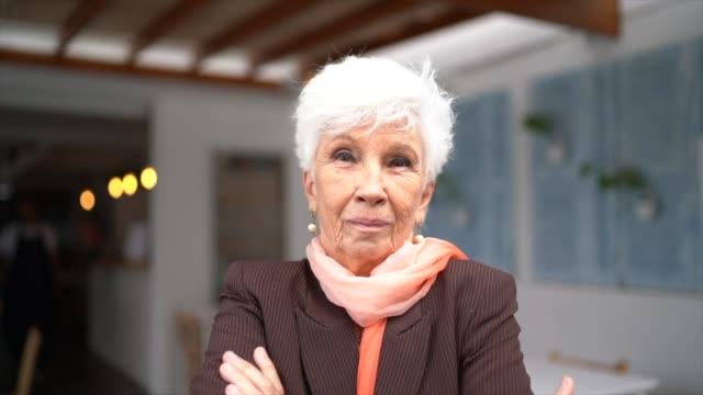 vídeos y material grabado en eventos de stock de retrato de una mujer mayor en el restaurante - brazos cruzados