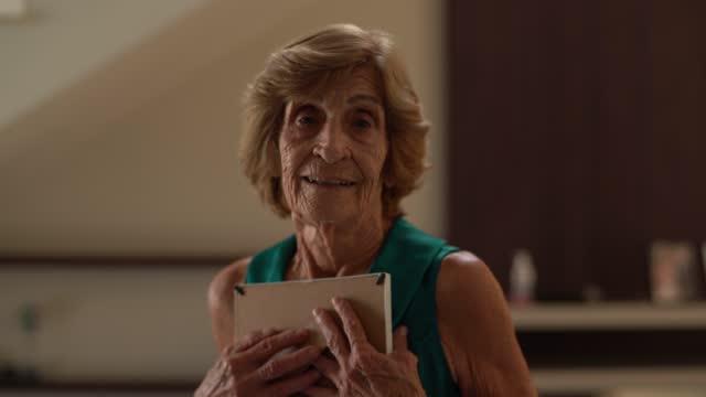 vídeos de stock, filmes e b-roll de retrato de uma idosa abraçando uma moldura em casa - nostalgia