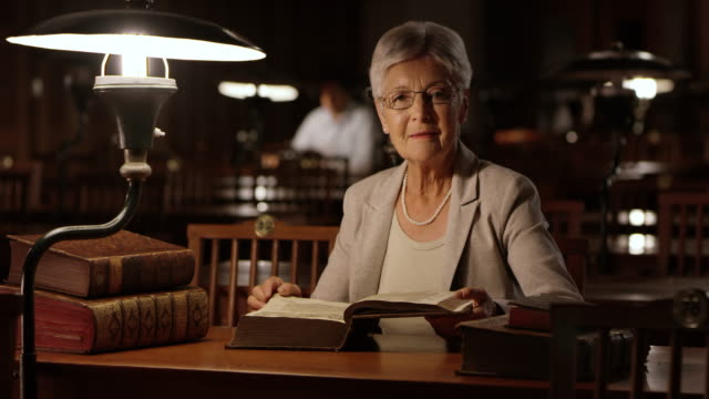 ds portrait of a senior woman reading in the library at night - study stock videos & royalty-free footage