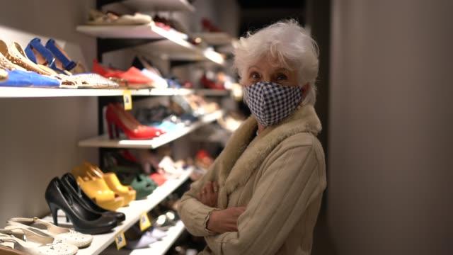 vídeos de stock, filmes e b-roll de retrato de uma idosa usando máscara facial comprando sapatos em um brechó - braços cruzados
