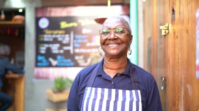 porträt einer seniorin, die vor dem restaurant arbeitet und steht - gastwirt stock-videos und b-roll-filmmaterial