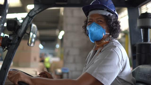 vídeos de stock, filmes e b-roll de retrato de uma idosa trabalhando em uma fábrica / armazém dirigindo uma empilhadeira - capacete de trabalho