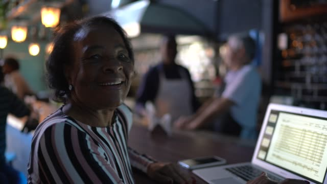 portrait of a senior woman working in a restaurant - baby boomer stock videos & royalty-free footage