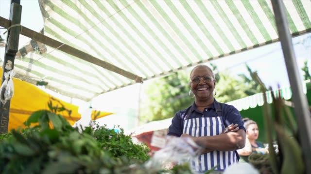 vídeos de stock e filmes b-roll de portrait of a senior woman working in a street market - mercado de produtos agrícolas