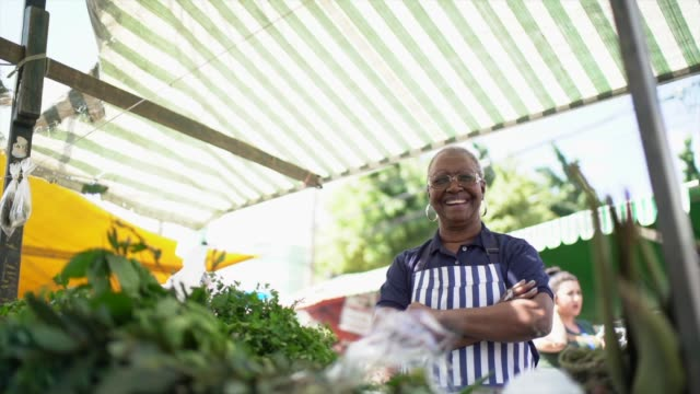 portrait of a senior woman working in a street market - farm produce market stock videos & royalty-free footage