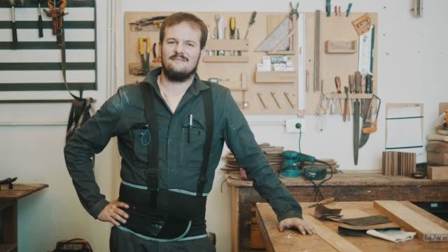 vidéos et rushes de portrait d'un charpentier sérieux (ralenti) - artisant
