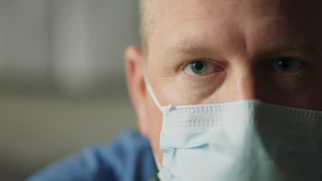 slo mo cu portrait of a serious doctor wearing ppe removing his face shield - positive emotion点の映像素材/bロール