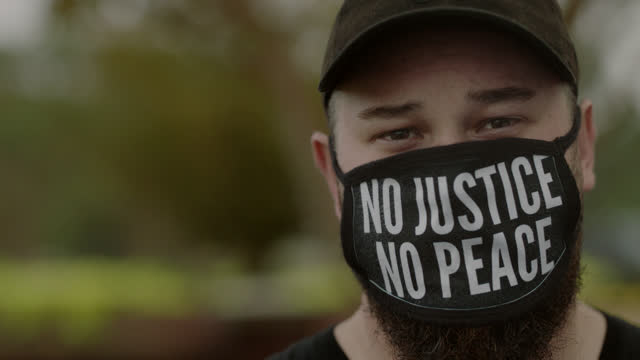 slo mo cu portrait of a serious man wearing a black lives matters mask - unfairness stock videos & royalty-free footage