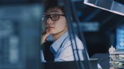 Portrait of a Serious Professional Japanese Development Engineer Thinking at His Work Place in a High Tech Research Laboratory with Modern Computer Equipment.