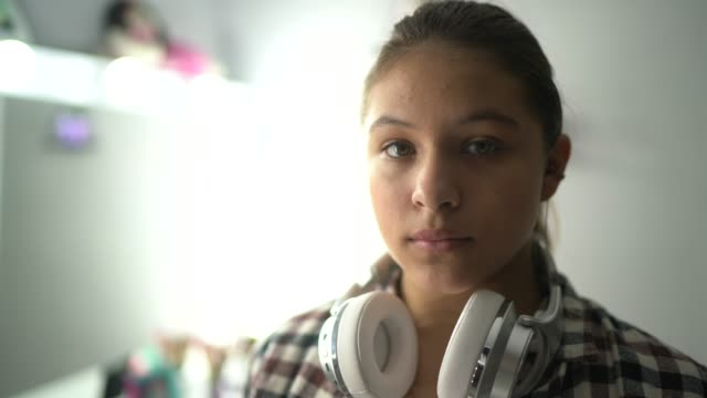 portrait of a serious teenager girl at home - serio video stock e b–roll