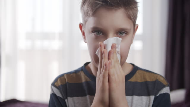 portrait of a sick boy cleaning his nose - facial tissue stock videos & royalty-free footage