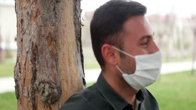 vídeos de stock, filmes e b-roll de retrato de um homem doente usando máscara médica em um parque público da cidade. - obscured face