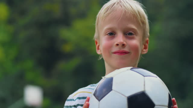 portrait of a small boy catching a football in the playground - childhood stock videos & royalty-free footage