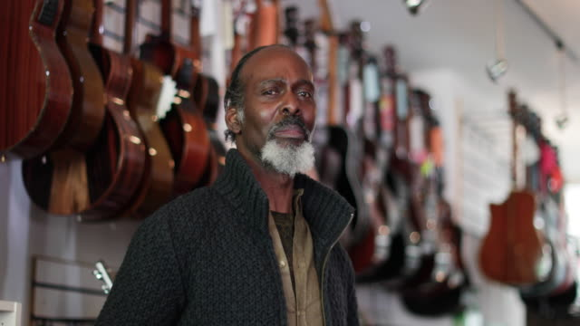portrait of a small business owner in a guitar store - 40 seconds or greater stock-videos und b-roll-filmmaterial