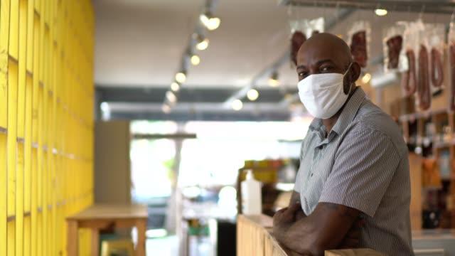 vídeos de stock, filmes e b-roll de retrato de um pequeno empresário usando máscara facial - braços cruzados