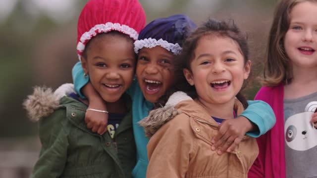 slo mo portrait of a small diverse group of preschool girls embracing, laughing - vanliga människor bildbanksvideor och videomaterial från bakom kulisserna