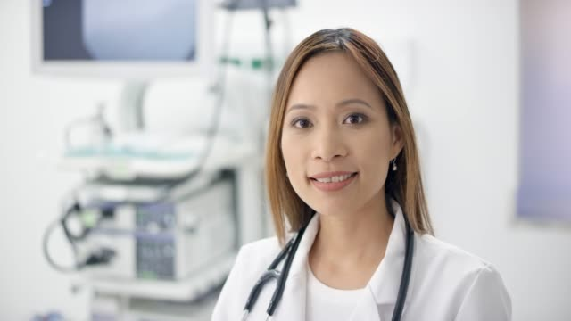 portrait of a smiling asian female doctor standing in her office and smiling - part of a series stock videos & royalty-free footage
