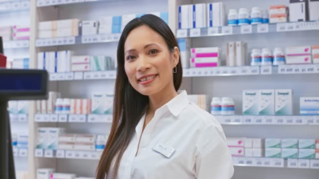 portrait of a smiling asian female pharmacist standing behind the counter - business finance and industry stock videos & royalty-free footage