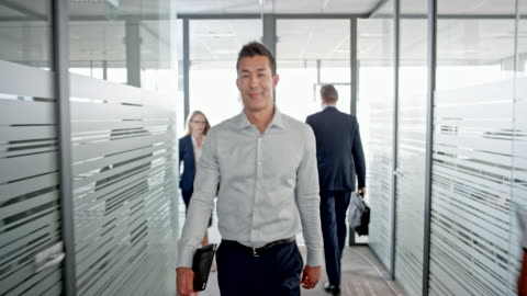 portrait of a smiling asian man walking in the office hallway and looking into the camera - large group of people stock videos & royalty-free footage