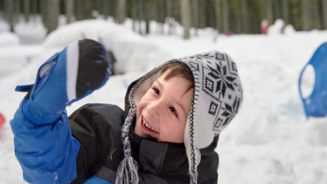 slo mo portrait of a smiling boy waving in the snowy playground - sports glove stock videos and b-roll footage
