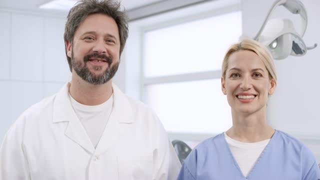 vídeos de stock, filmes e b-roll de retrato de um dentista de macho caucasiano sorridente e seu assistente feminina - dentista