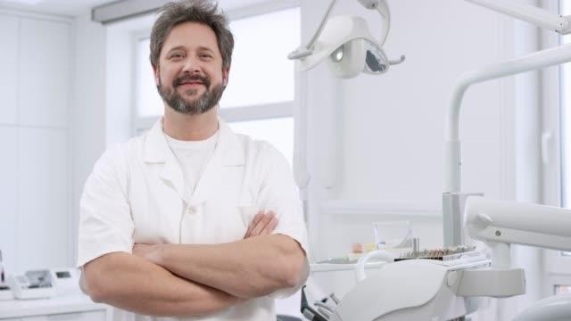 vídeos de stock, filmes e b-roll de retrato de um dentista de macho caucasiano sorridente - dentista