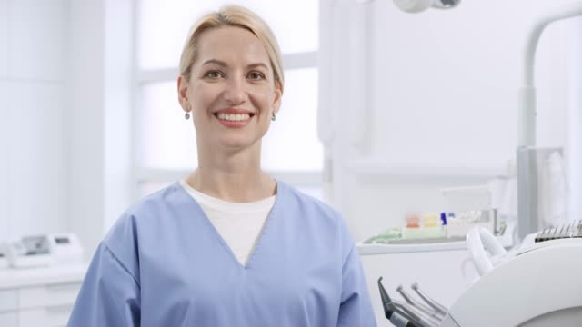portrait of a smiling caucasian oral hygienist - orecchini video stock e b–roll