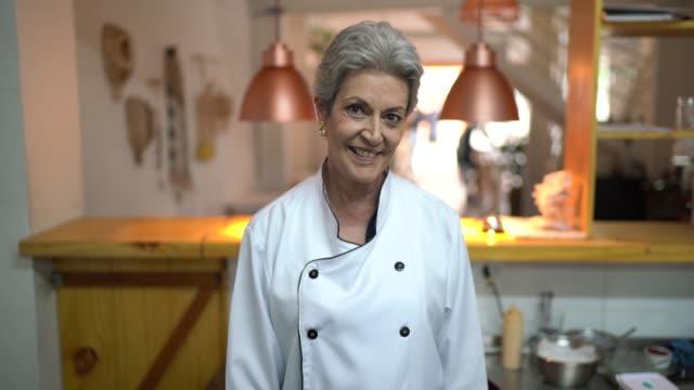 vidéos et rushes de verticale d'un chef de sourire à son restaurant - cuisinière