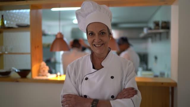 vídeos de stock, filmes e b-roll de retrato de um cozinheiro chefe de sorriso em seu restaurante - dedicação