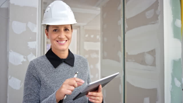 portrait of a smiling female architect standing in the building and looking at the plans on her digital tablet - renovation stock videos & royalty-free footage