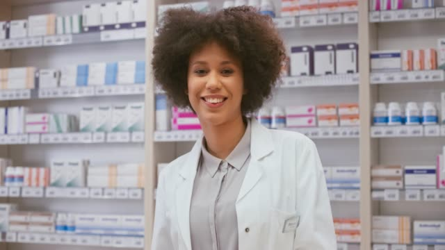portrait of a smiling female pharmacist standing behind the counter at the drugstore - medical supplies stock videos & royalty-free footage