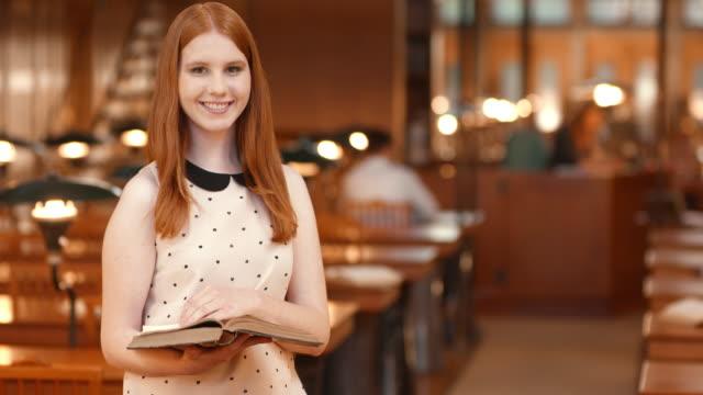 DS porträtt av en leende kvinnlig student står i biblioteket